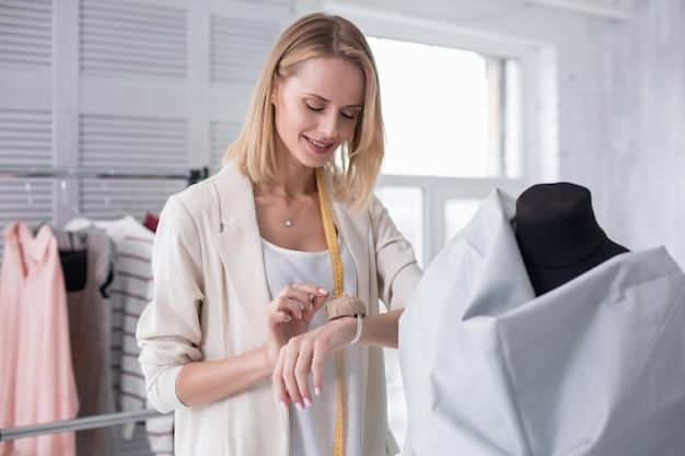 Maatwerkproces. blij dat vrouwelijke kleermaker een pin neemt terwijl ze naar beneden staart