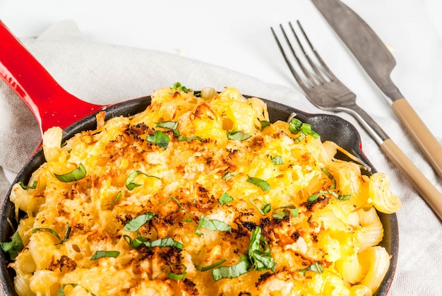 Mac en kaas, macaronipasta in amerikaanse stijl met kaasachtige saus en knapperige paneermeel topping, in geportioneerde pan, witte marmeren tafel, copyspace