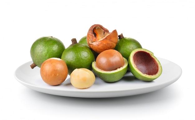 Macadamia noot in een plaat geïsoleerd op een witte achtergrond