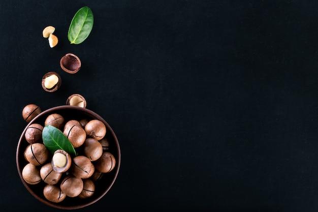Macadamia noten in plaat met granen en bladeren op zwart