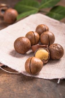 Macadamia noten stapel met schelpen in zak op houten tafel