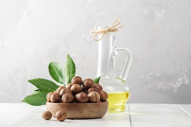 Macadamia-olie. kom met macadamia noten op een witte houten tafel.