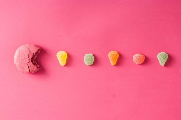 Macaron met gelei bonen op roze muur. plat leggen