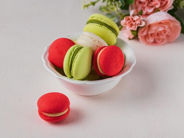 Macaron of makaron franse coockie op lichte achtergrond met lente bloemen, pastel kleuren.