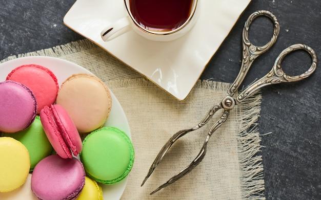Macaron, oude tang voor taarten, kopje thee, servet, bovenaanzicht