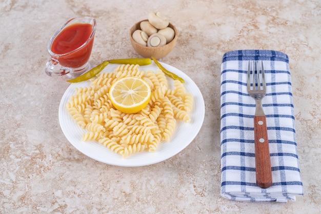 Macaroni die naast een vork wordt geserveerd, vergezeld van porties ketchup en champignons op een marmeren oppervlak