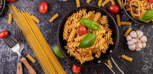 Macaroni gebakken met tomaten en basilicum in de pan