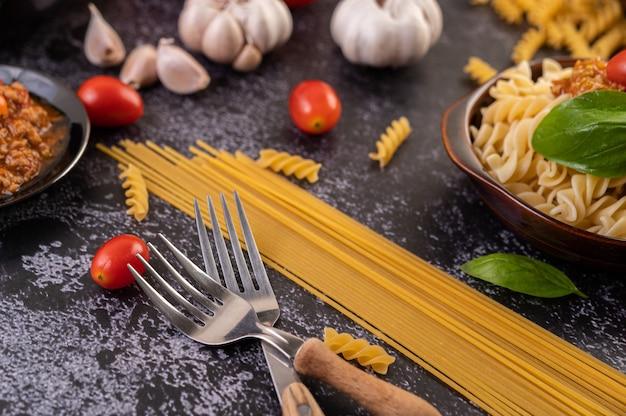 Macaroni gebakken met tomaten en basilicum op een grijze plaat.