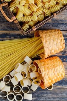 Macaroni in een emmer en dienblad met pasta en spaghetti bovenaanzicht op een donkere houten achtergrond