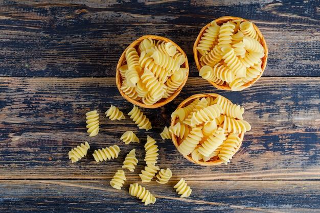 Macaroni in kleine emmers op een donkere houten achtergrond. bovenaanzicht.