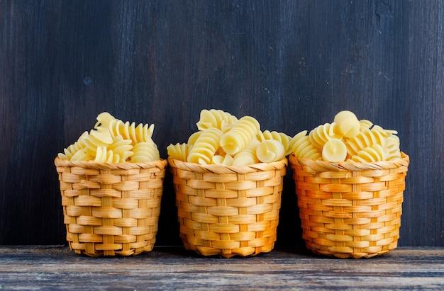Macaroni in kleine emmers op een donkere houten achtergrond. zijaanzicht. ruimte voor tekst