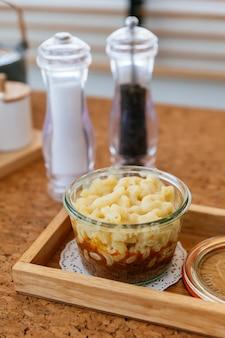 Macaroni-kaas gebakken met vleessaus in glazen kom op houten plaat met zout, peper en bestek.
