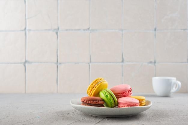 Macaroni koekjes op een bord en een kopje espresso