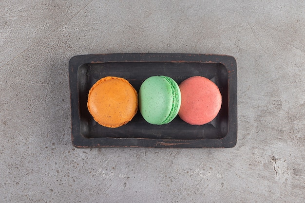 Macaroni-koekjes van verschillende kleuren in een donkere houten plank.