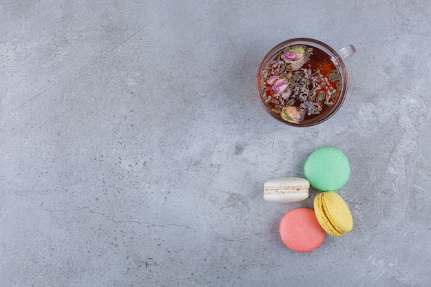 Macaroni koekjes van verschillende kleuren met een glazen kopje kruidenthee.