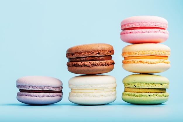 Macaroni-koekjes van verschillende kleuren zijn gerangschikt in de vorm van piramidestappen op een blauwe achtergrond.
