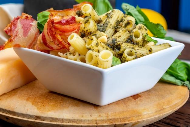 Macaroni met pesto (penne rigate). met ui en spek, kaas, basilicum, pijnboompitten, knoflook. op een houten tafel met een rustieke uitstraling.