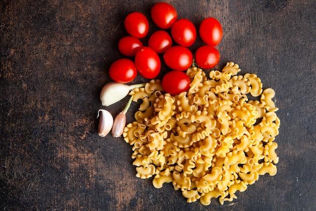 Macaroni met tomaten en knoflook bovenaanzicht op een donkere gestructureerde achtergrond