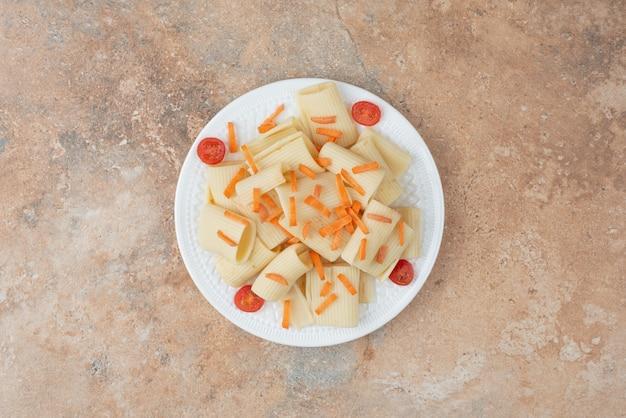 Macaroni met wortel en tomatenkers op witte plaat.
