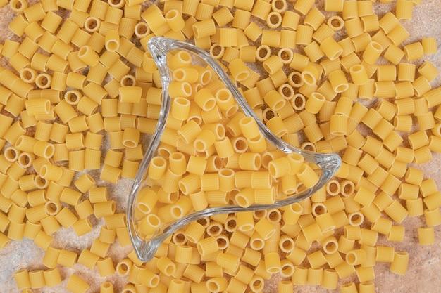 Macaroni pasta in een kleine glazen plaat op marmeren ruimte.