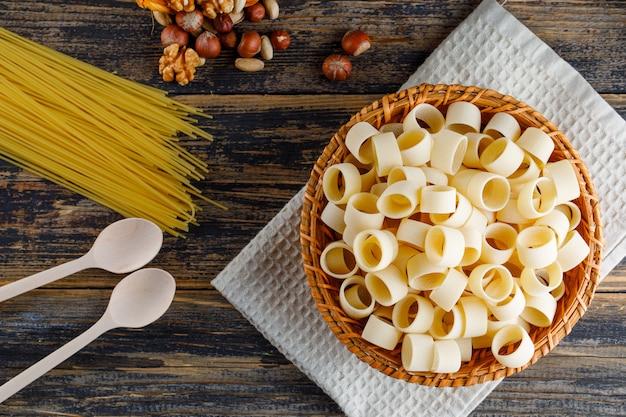 Macaroni pasta in een mand met spaghetti, lepels, verschillende noten bovenaanzicht op een houten achtergrond