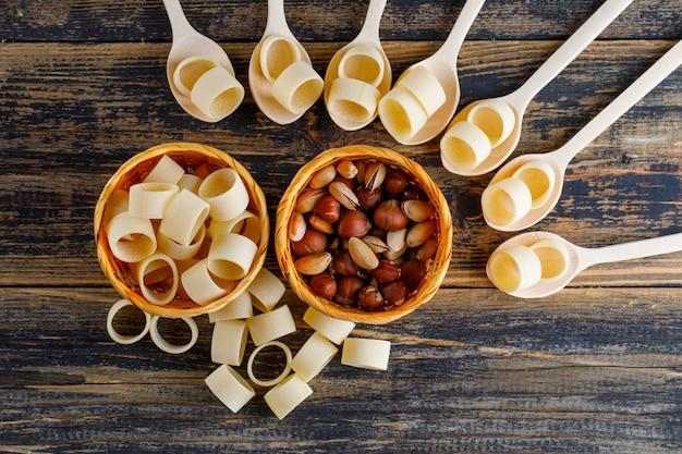 Macaroni pasta in kommen en lepels met pistache en hazelnoot bovenaanzicht op een donkere houten achtergrond