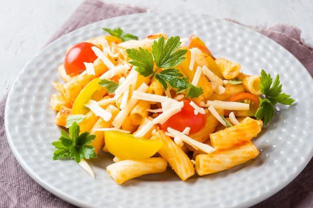 Macaroni, pasta in tomatensaus en kaas in een bord op een woode