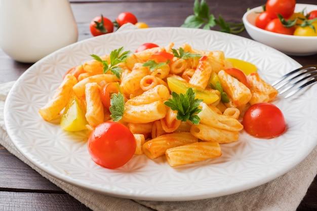 Macaroni, pasta in tomatensaus en kaas in een plaat op een houten tafel