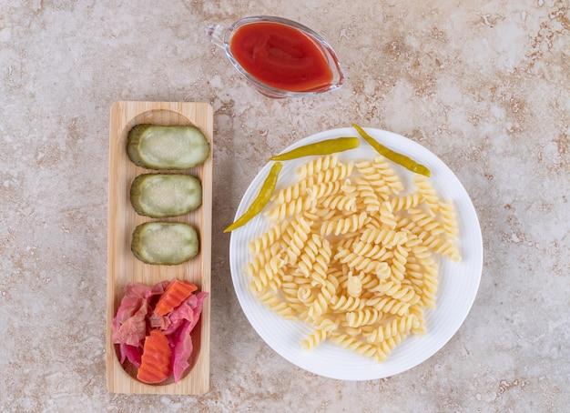 Macaroni vergezeld van een dienblad met diverse augurken en een portie ketchup op marmeren ondergrond.