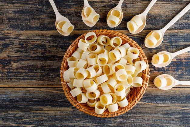 Macaronideegwaren in een kom en lepels op een donkere houten achtergrond. bovenaanzicht.