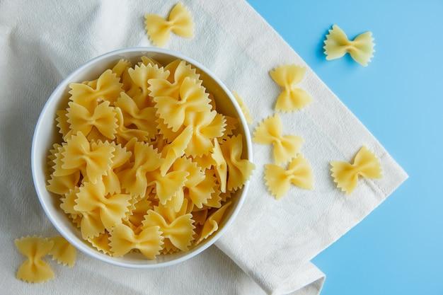 Macaronideegwaren in een kom op een doek en cyaan blauwe achtergrond. bovenaanzicht.