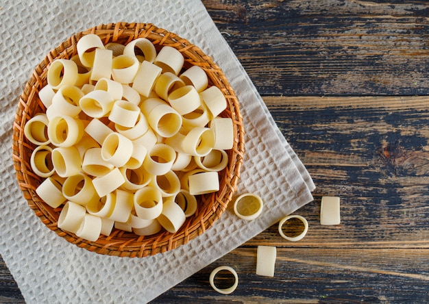Macaronideegwaren in een kom op een doek en een houten achtergrond. bovenaanzicht. ruimte voor tekst