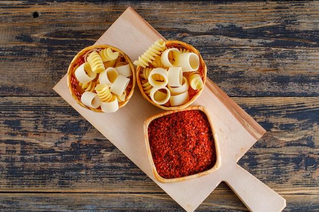 Macaronideegwaren in emmers met rode kruid hoogste mening over een scherpe raad en een houten achtergrond