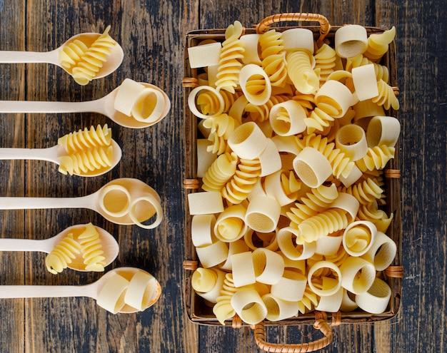 Macaronideegwaren in lepels en mand op een houten achtergrond. bovenaanzicht.