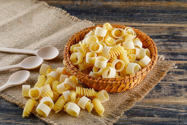 Macaronideegwaren met lepels in een kom op jute en houten achtergrond, hoge hoekmening.