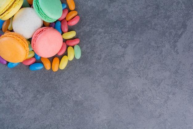 Macaronikoekjes van verschillende kleuren die op geleibonen worden geplaatst