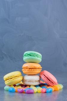 Macaronikoekjes van verschillende kleuren die op geleibonen worden geplaatst.