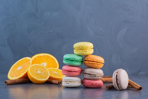 Macaronikoekjes van verschillende kleuren met gesneden citroen en pijpjes kaneel.