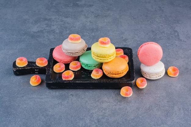 Macaronikoekjes van verschillende kleuren met kleverig suikergoed