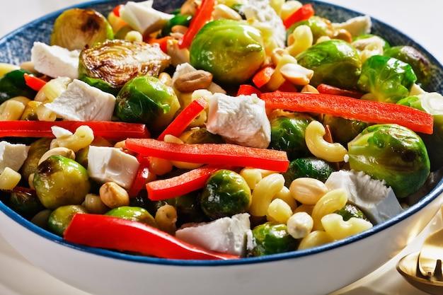 Macaronisalade met broccolispruiten, paprikareepjes, feta en pinda in een kom, horizontale weergave van bovenaf, close-up