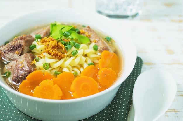 Macaronisoep met varkensvlees en wortel op witte houten lijst
