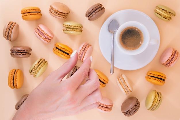 Macarons en een espresso op een pastel oppervlak met een hand die probeert een macaron te stelen