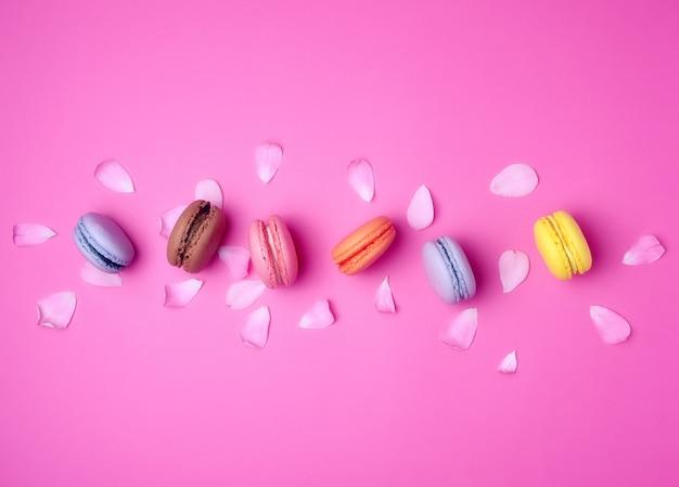 Macarons met room en een roze roze knop met verspreide bloemblaadjesachtergrond