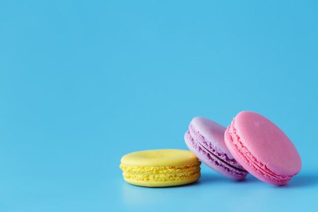 Macarons op blauwe achtergrond met ruimte voor kopie ruimte