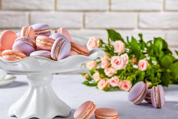 Macarons op een taartplateau van wit porselein. mooi boeket rozen en bakstenen muur aan de oppervlakte, close-up