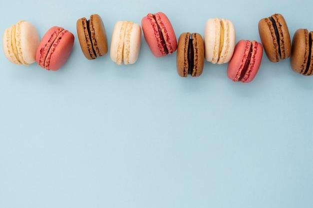 Macaronscakes in rij op blauwe achtergrond. plat lag sociale media walpa