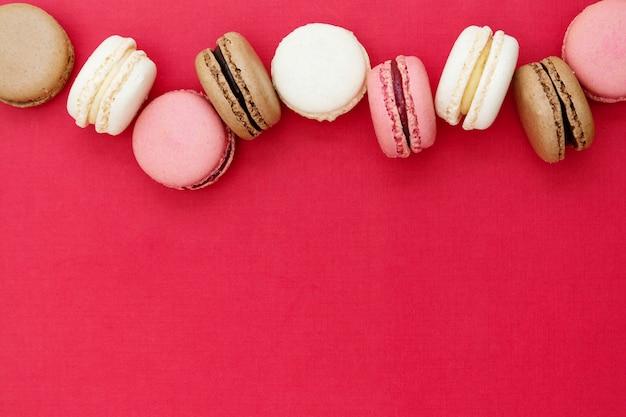 Macaronscakes of koekjes over rode achtergrond. plat leggen. kopieer ruimte.
