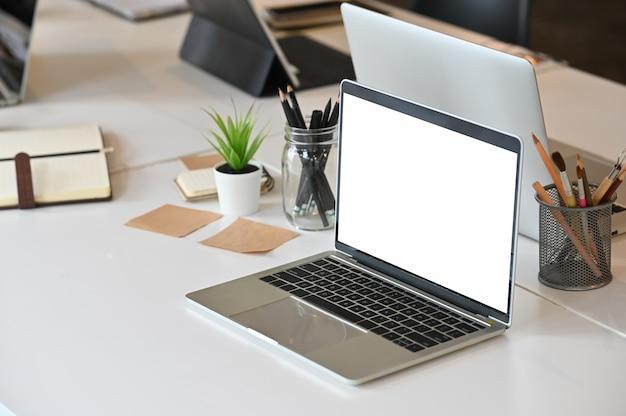 Macbook-laptopcomputer met het lege scherm op creatieve vergaderzaal.