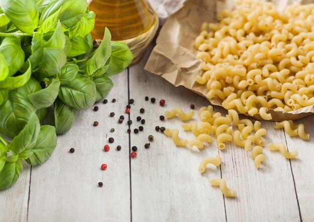 Maccheroni ellebogen klassieke rauwe pasta in bruin papier op lichte houten tafel achtergrond met basilicum en olie.