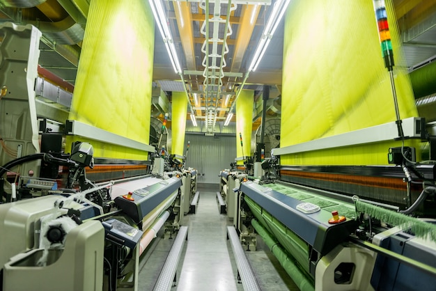 Machine en apparatuur in de weverij. interieur van industriële textielfabriek. weefgetouw